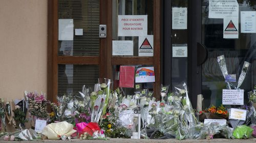 Flowers lay at the entrance of the school where a slain history teacher was teaching, Saturday, Oct. 17, 2020 in Conflans-Sainte-Honorine, northwest of Paris