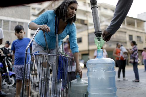Locals in Venezuela venture the streets far and wide for rare sources of fresh water as mass blackouts continue throughout the country.