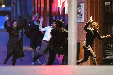 People flee from the Lindt Cafe, Martin Place during a hostage standoff on December 16, 2014 in Sydney, Australia. Police stormed the Sydney cafe  where lone gunman, Man Haron Monis, had been holding ten customers and eight employees. Hostage Tori Johnson was killed by Monis and hostage Katrina Dawson was killed by a police bullet ricochet during the raid. Monis was killed by police.