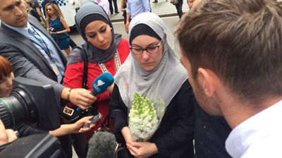 A Muslim woman visits the scene of the Lindt Cafe siege, carrying a bunch of flowers, to pay her respects. (Supplied)