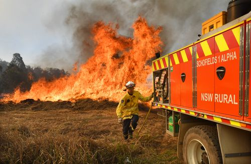 New South Wales Rural Fire Service firefighters are seen back burning and fighting fires on Long Gully Road in the northern New South Wales town of Drake. (AAP Image/Darren England)
