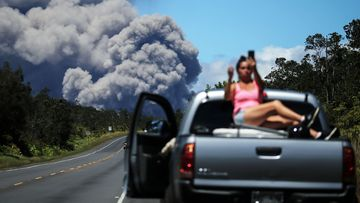 A woman takes a photo as an ash plume rises from the Kilauea volcano on Hawaii's Big Island on May 15, 2018.