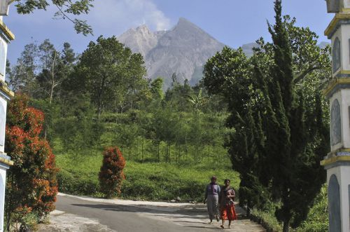 Villagers walk as Mount Merapi is seen in the background in Pemalang, Central Java. Picture: AAP