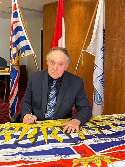 Gary Foster, Mayor of Northern Rockies, a municipality in northeastern British Columbia, Canada, signs the flag
