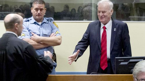 Ratko Mladic smiles as he greets his lawyers at the Hague's war crimes tribunal. (AAP)