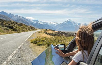 Woman checking paper map on a highway