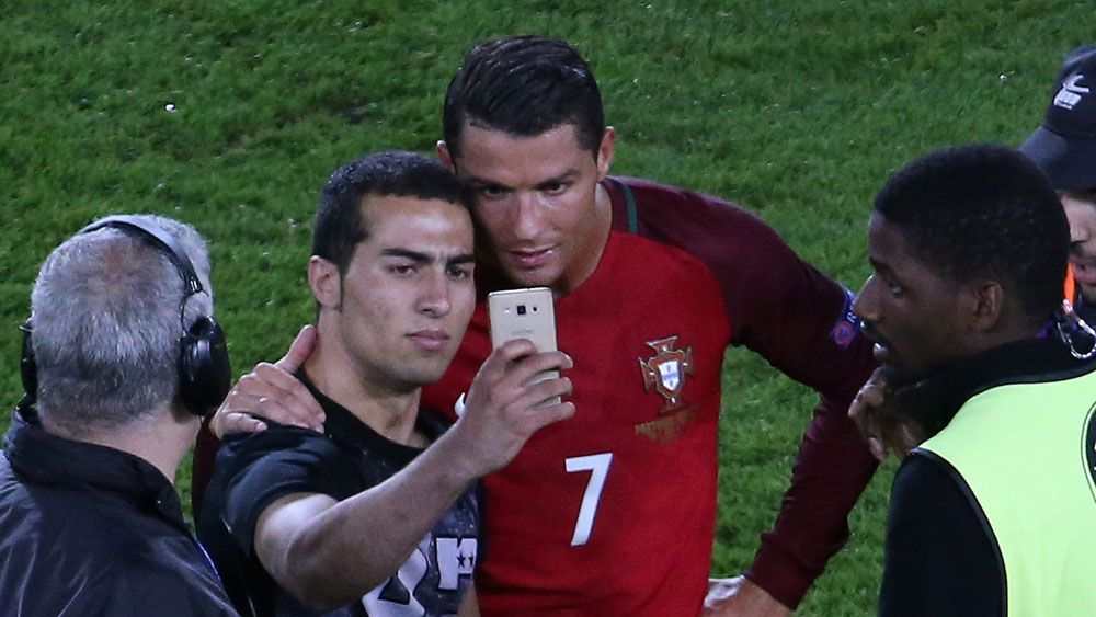 Ronaldo poses with pitch invader