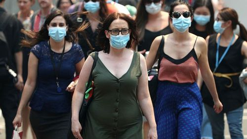 People wear face masks to protect from smoke haze as they cross a busy city street in Sydney, Australia. Smoke haze continues to hang over the city as bushfires burn across New South Wales.