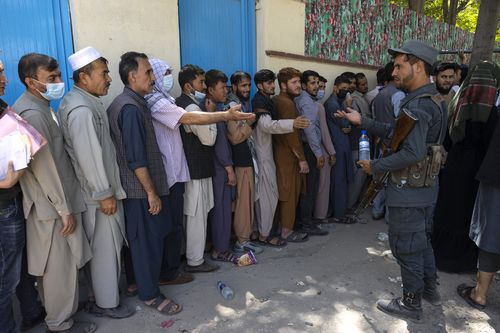 Afghans wait in long lines for hours at the passport office as many are desperate to have their travel documents ready to go (Photo by Paula Bronstein /Getty Images)