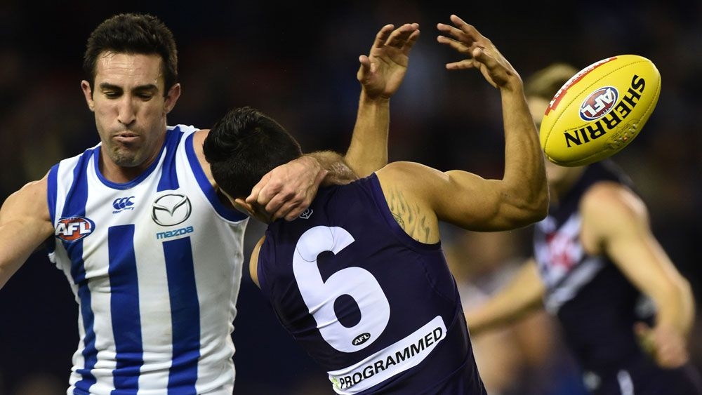 North Melbourne's Michael Firrito (left) makes a high tackled on Fremantle Dockers player Danyle Pearce. (AAP)