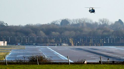 A police helicopter flies over the runway at Gatwick Airport, London, as the airport remains closed with incoming flights delayed or diverted to other airports, after drones were spotted.