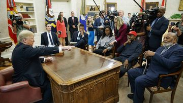 President Donald Trump, left, meets with rapper Kanye West, seated second from right, in the Oval Office of the White House in Washington on October. 11, 2018.