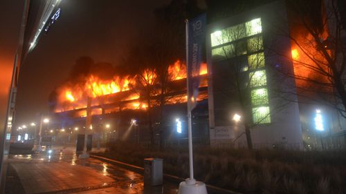 An estimated 1400 cars were destroyed after a huge fire raged through a multi-story parking garage in the northern English city of Liverpool. (AAP)