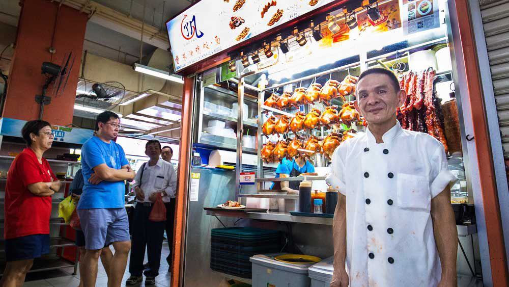 Singapore-based chef Chan Hon Meng pictured out the front of his Michelin star street stall Honk Kong Soya Sauce Chicken Rice & Noodles. Image: Supplied