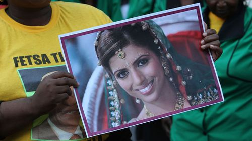 A womans rights activist outside protests outside the Western Cape High Court with a picture. (Getty Images)