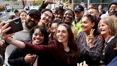 Jacinda Ardern taking a selfie with staff and students from Massey University.
