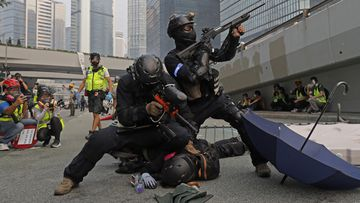 Police detain protestors during the demonstration in Hong Kong. Riot police fired tear gas after a large crowd of protesters at a Hong Kong shopping district ignored warnings to disperse in a second straight day of clashes, sparking fears of more violence ahead of China's National Day.