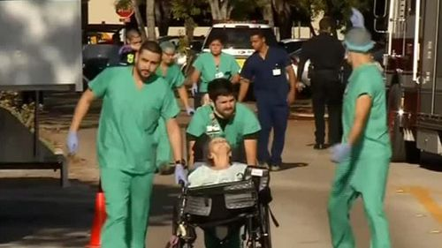 Emergency crews escort residents away from the Rehabilitation Center at Hollywood Hills. (Reuters)