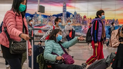 Travellers wearing protective masks exit the arrival hall at Hong Kong High Speed Rail Station amid the coronavirus outbreak.