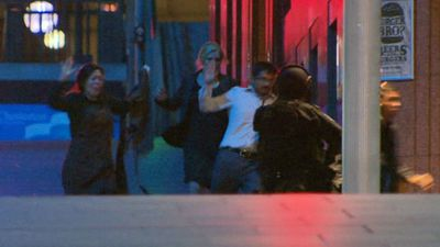 Suddenly a group of hostages ran from the cafe, catching police unaware. (9NEWS)