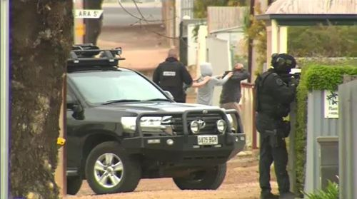 Earlier today, multiple residents in Wallaroo were led from their homes at gunpoint by heavily armed police as the search continued. Picture: 9NEWS