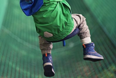 Little boy zipping on zip line in outdoors amusement park.
