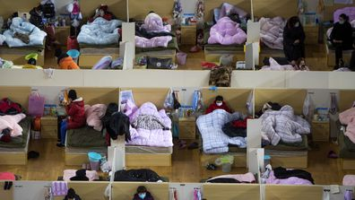 Patients infected with the coronavirus take rest at a temporary hospital converted from Wuhan Sports Centre in Wuhan.