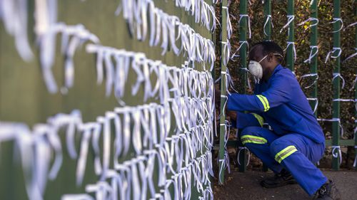 In this July 29, 2020 photo, Silva Cossa, the caretaker, ties ribbons onto the fence to represents a South African who has died from COVID-19, at St James Presbyterian church in Bedford Gardens, Johannesburg, South Africa.