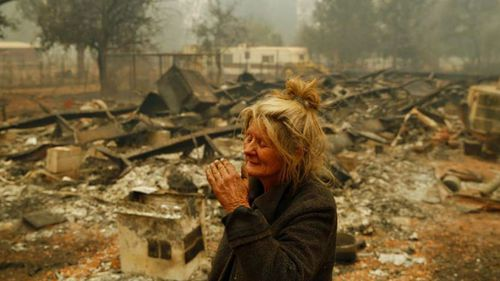 Cathy Fallon wipes her face as she stands near the charred remains of her home in Paradise, California.