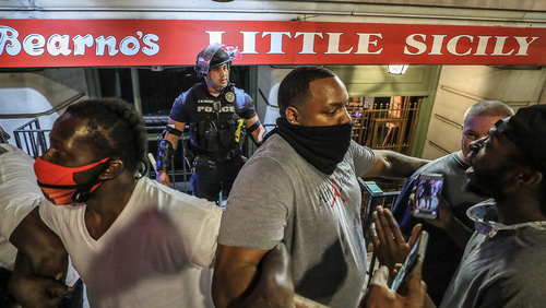 In this Thursday, May 28, 2020 photo, protesters rallying against police brutality surround a Louisville Metro Police Department officer in front of Bearno's restaurant, in Louisville, Ky.  (Michael Clevenger/Courier Journal via AP)