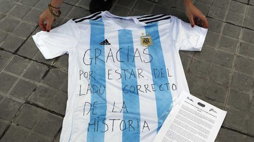 "A woman lays down an Argentina shirt with a message reading in Spanish: ""Thank you for being on the right side of the history"" in Barcelona, Spain. (AAP)"