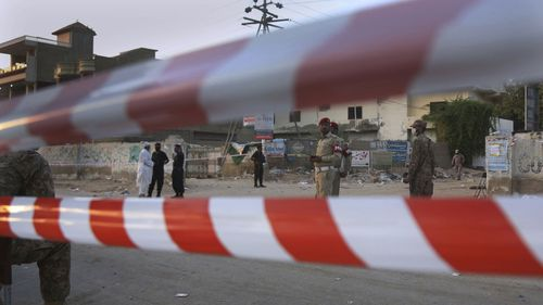 Pakistan army soldiers and police commandos stand guard while they cordon off a street leading to the site of a plane crash, in Karachi, Pakistan, Saturday, May 23, 2020.
