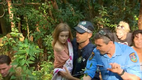 Police carry nine-year-old Natalya from the bush, 24 hours after she vanished. (9NEWS)