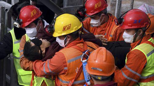 在新华社发布的这张照片中,救援人员将一名矿工拖入了中国东部山东省栖霞市的一辆地雷中,救护车。