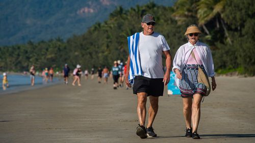 People walk along a beach in North Queensland as Cairns faces fear of COVID-19 and takes a three-day lockdown.