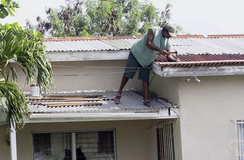 A homeowner makes last minute repairs to his roof in preparation for Hurricane Irma, in St. John's, Antigua and Barbuda. (AP)