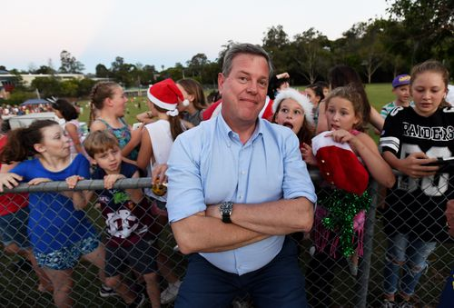Tim Nicholls with schoolchildren behind him after doing a live cross at the Jindalee State School Christmas carols. (AAP)
