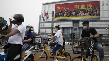 Residents ride past Chinese military propaganda with the slogan 'Heroic' in Beijing.