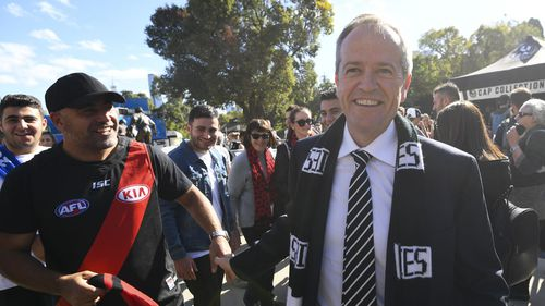 Bill Shorten speaks to a fan as he arrives to watch the ANZAC Day game between Essendon and Collingwood at the MCG.