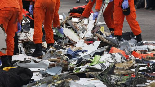 Indonesian rescue team members collecting the remains of the crashed plane at Tanjung Priok Harbour.