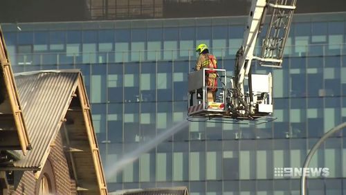 Fire crews brought in cranes to help battle the remnants of the blaze. (9NEWS)