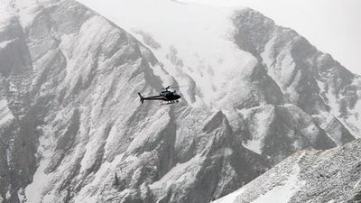 A search and rescue helicopter scours the crash site. (AAP)
