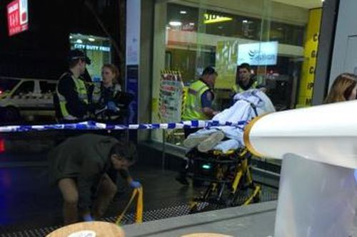 A man is taken away on a stretcher after the brawl on Bourke Street in Melbourne's CBD.