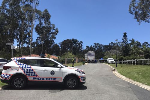 Police officers and detectives are seen at the scene of the discovery of a woman's body on the street outside her home in Worongary. (AAP)