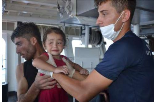A little girl is treated by members of the coast guard after the migrant boat capsized off the coast of Cyprus. Picture: Getty