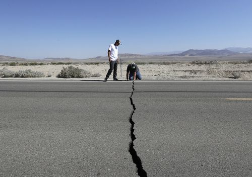 Ron Mikulaco and his nephew, Brad Fernandez, examine a crack caused by an earthquake on Highway 178, July 6, 2019, outside of Ridgecrest, California.
