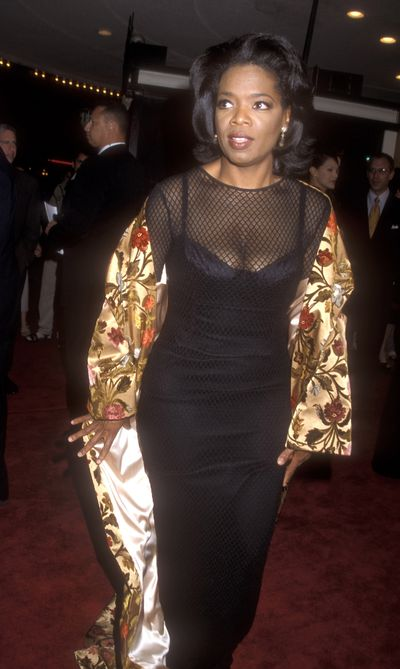 Shimmering in a gold cape and black mesh dress in 1998