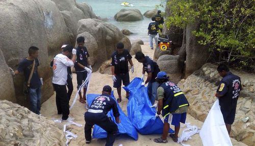 Thai officers walk near bodies of two British tourists on a beach on Koh Tao island in September 2014. (AAP)