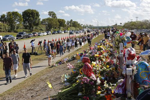 Parents and students walk by the memorial for the victims of the shooting. (AAP)