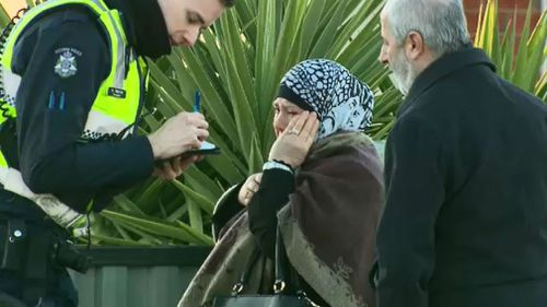A distressed neighbour speaks with police. (9NEWS)